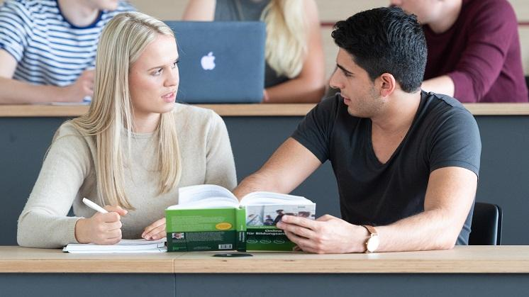 Two bachelor students sitting in a classroom discussing an article in a book
