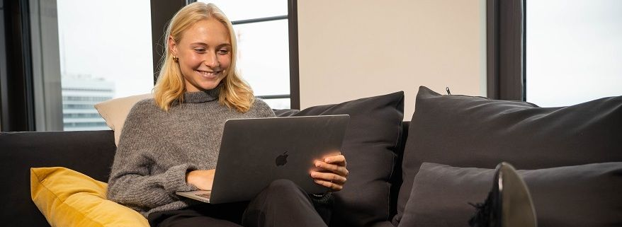 Lächelnde blonde Studentin im Bachelor of Arts am Laptop